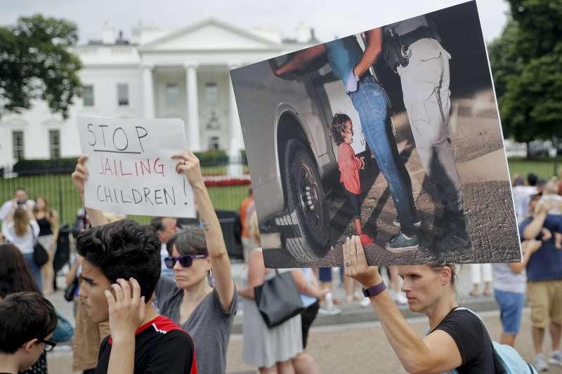 6月21日,美國民眾舉著印了宏都拉斯2歲女童在邊境哭泣照片的標牌在白宮前抗議(美聯社)