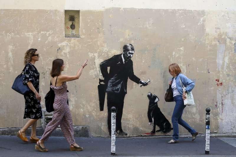 2018年6月25日,民眾經過英國知名街頭藝術家班克西(Banksy)在巴黎的最新塗鴉。(AP)