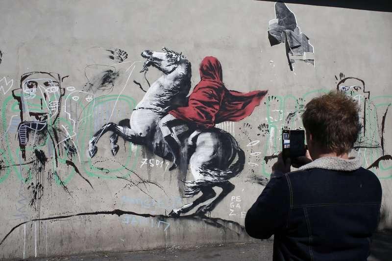 2018年6月25日,民眾拍攝英國知名藝術家班克西(Banksy)在巴黎的最新塗鴉。(AP)