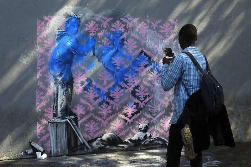 2018年6月25日,民眾於英國知名街頭藝術家班克西(Banksy)在巴黎的最新塗鴉前拍照。(AP)