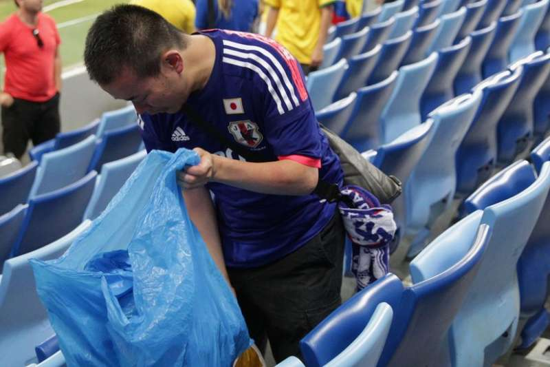 日本球迷把加油道具在賽後當成垃圾袋清理環境。(BBC中文網)