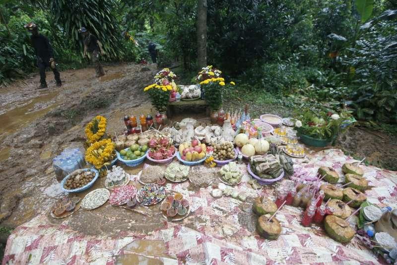 泰國青少年足球隊及其教練23日在清萊府美塞縣的洞穴失蹤,他們的家屬準備供品拜拜祈禱(美聯社)
