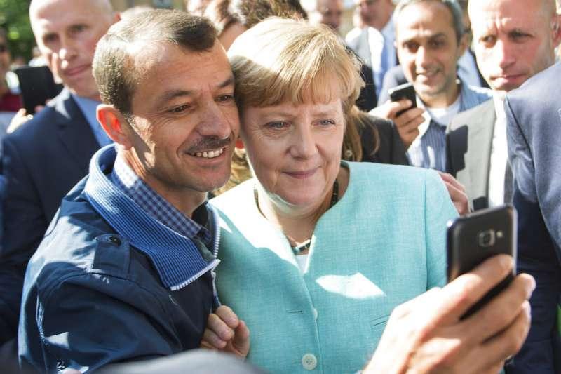 德國總理梅克爾2015年與移民自拍合照。(AP)