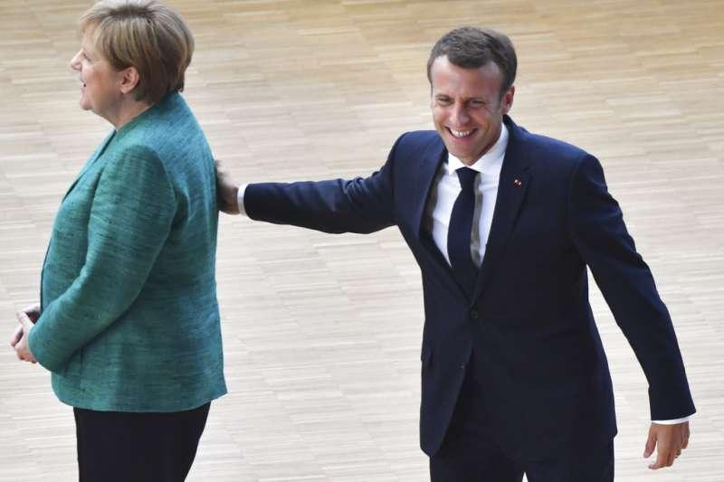 2018年6月28日,法國總統馬克宏在布魯塞爾輕拍德國總理梅克爾。(AP)