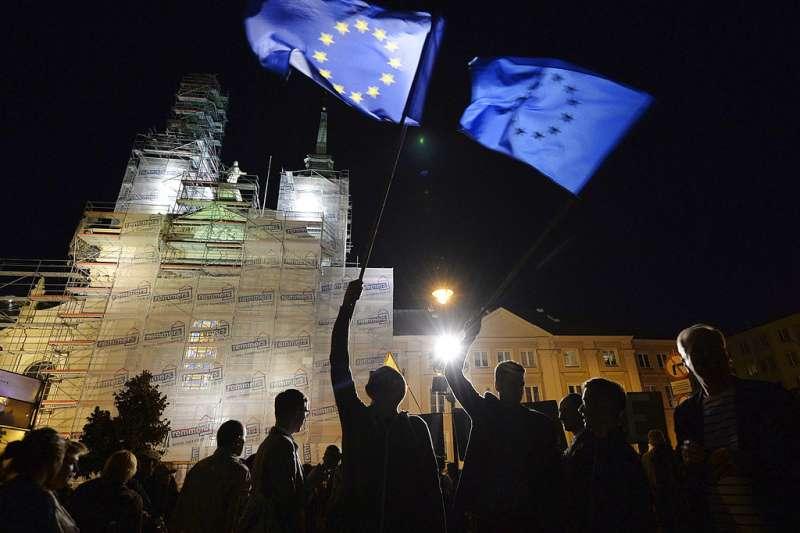 2018年7月3日,波蘭民眾抗議政府推動法官退休法案,箝制司法獨立,在首都華沙的最高法院前高舉歐盟旗幟。(AP)
