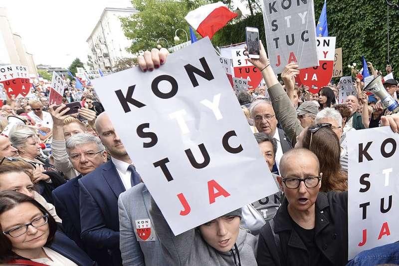 2018年7月4日,波蘭民眾不滿政府推動法官退休法案,箝制司法獨立,在首都華沙高舉憲法標語。(AP)