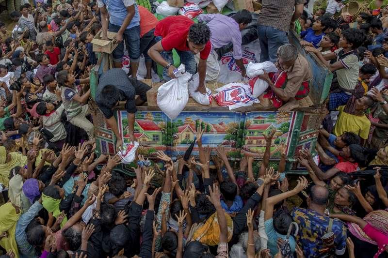 位於孟加拉難民營的羅興亞難民爭先恐後的領物資。(美聯社)