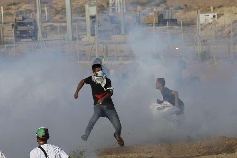 在加薩走廊邊境躲避以色列催淚瓦斯攻擊的巴勒斯坦人。(美聯社)