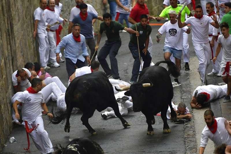 2018年7月6日,西班牙奔牛節「聖費爾明節」開幕,民眾在潘普洛納街頭跑給鬥牛追。(AP)