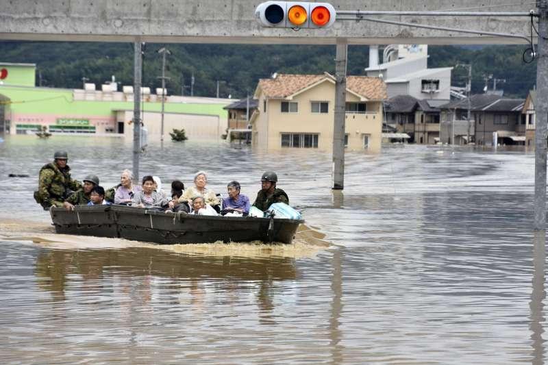 今年第7號颱風巴比侖侵襲日本,在西部和中部造成破紀錄豪雨,自衛隊員和警消正在營救遭困的年長者。(美聯社)