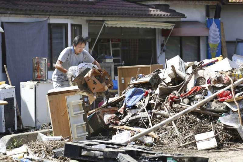 日本岡山縣總社市一位災民正在清理家園。(美聯社)