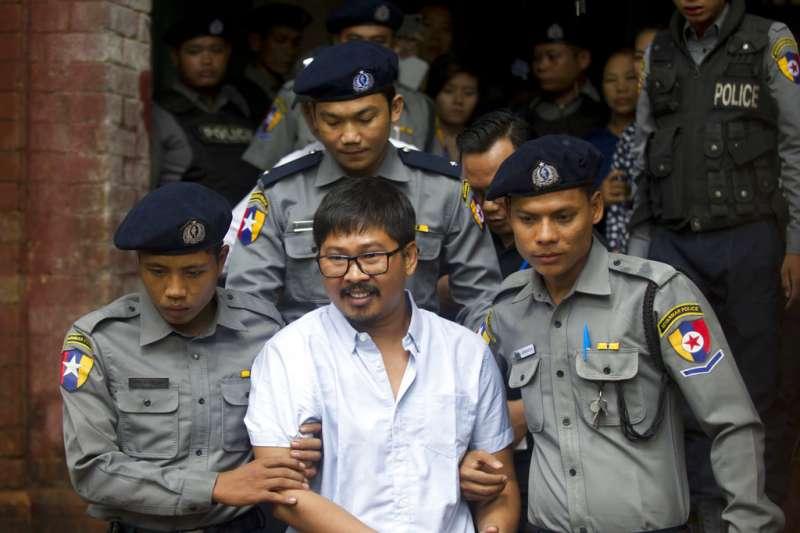 2018年7月9日,遭逮捕的緬甸路透社記者瓦隆(Wa Lone)在警方戒護下步出法院,他與記者吳覺梭被控違反緬甸政府機密法。(AP)
