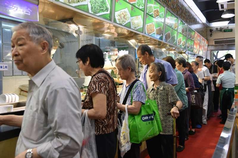 老人們在廣州天河區石牌街道的指定助餐點排隊取餐。(新華社)