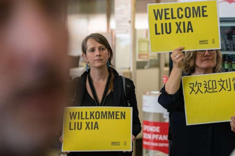 劉霞到達德國柏林時,有民間組織人士到機場舉起標語歡迎。(BBC中文網)