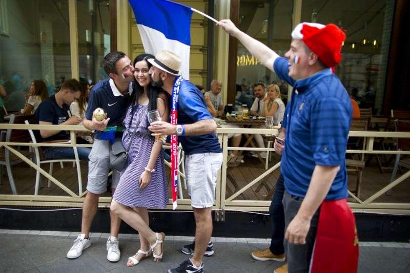 一群法國球迷在莫斯科街頭與一位俄羅斯女性合照。(美聯社)