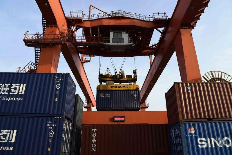 在青島膠州灣國際物流園,龍門塔吊在往中亞(青島)國際班列上裝載貨物。(新華社)