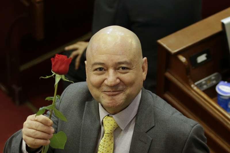 哥倫比亞前叛軍組織轉型為左翼政黨,20日正式進入國會,成員洛札達(Carlos Lozada)手拿玫瑰花。(美聯社)