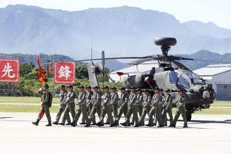 在臺灣阿帕契部隊成軍儀式上,一組飛行員走過一架AH-64E阿帕契武裝直升機。(AP)