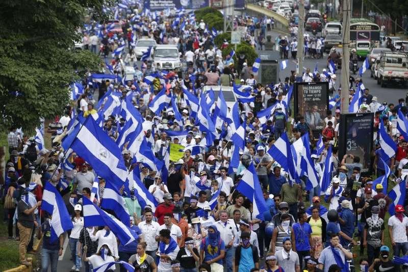 2018年7月23日,尼加拉瓜反政府示威,抗議者高舉尼國國旗,要求總統奧蒂嘉下台。(資料照,美聯社)