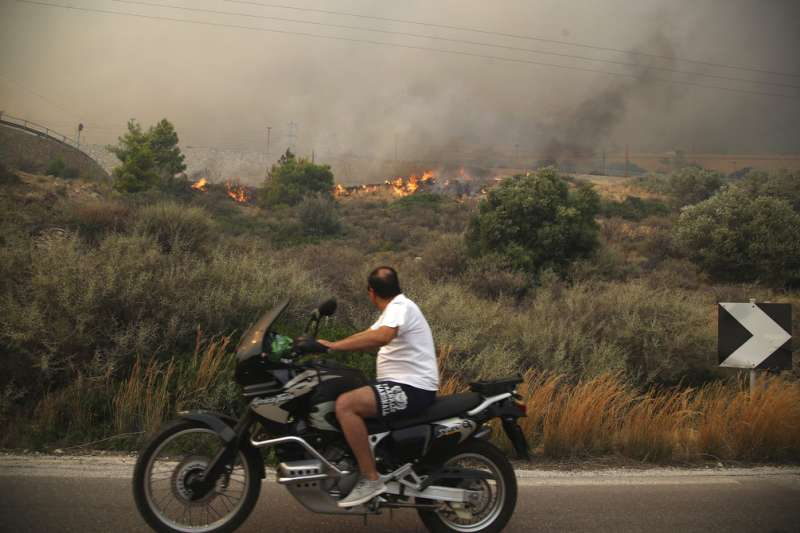 希臘發生10年來最嚴重的森林大火,雅典以西約55公里的基內塔(Kineta)附近森林仍有火光。(AP)
