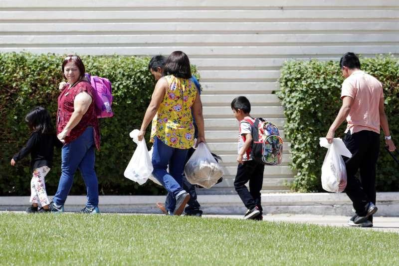 2018年7月26日,抵達鳳凰城一家收容中心的孩童與社工。(AP)