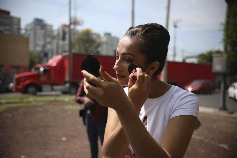 芭蕾舞者在墨西哥市街頭化妝,準備在紅燈時開始表演。(美聯社)