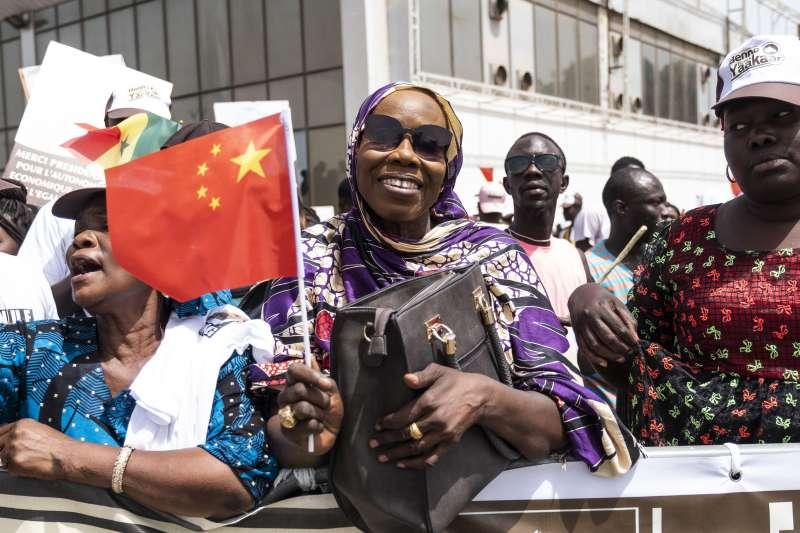 塞內加爾的民眾揮舞五星旗歡迎習近平。(美聯社)