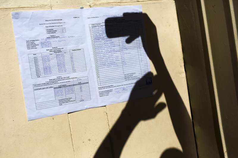 辛巴威選舉:民眾翻拍投票所開票結果。(AP)