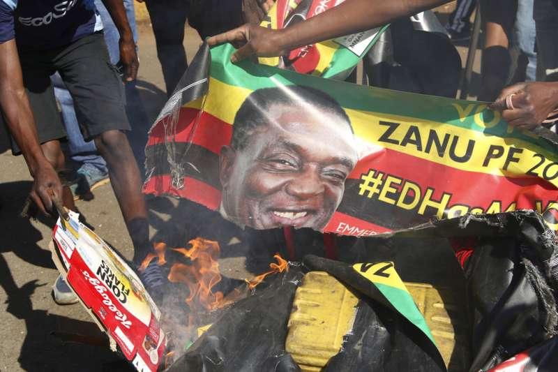 辛巴威選舉:反對派民眾燒毀總統姆納加瓦(Emmerson Mnangagwa)競選海報。(AP)