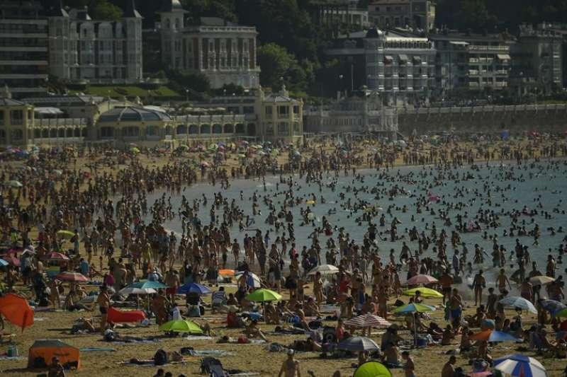 西班牙北部聖塞巴斯提安市(San Sebastian)的民眾前往海邊戲水消暑。(圖片來源:AP)