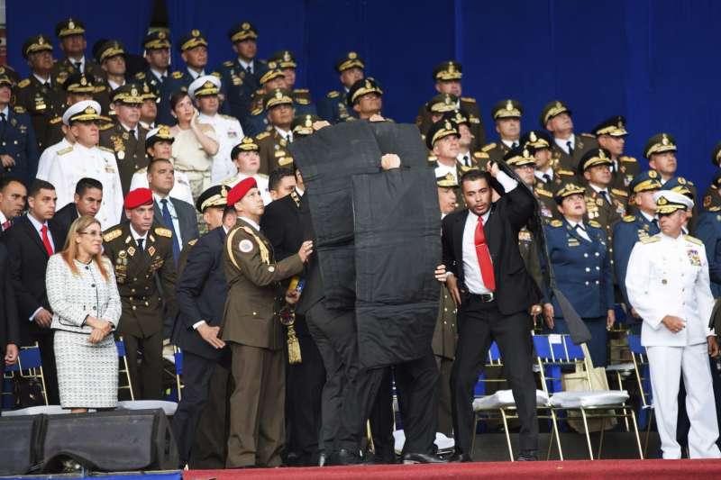 委內瑞拉國民警衛隊成立81周年紀念活動上發生爆炸,隨扈上台保護總統馬杜洛。(美聯社)