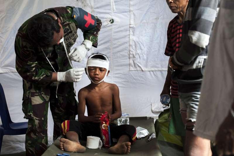 印尼龍目島卡亞甘地區在5日強震中受災嚴重,印尼軍方的急救護理人員症幫一名頭部受傷的男孩包紮(AP)
