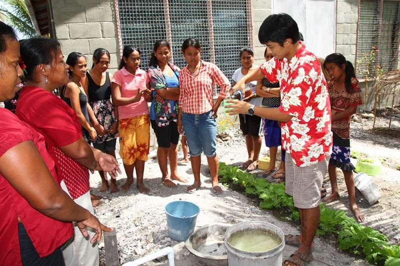 吉里巴斯技術團技師李宜龍(右二)指導農民使用尿液肥料。(國合會提供)