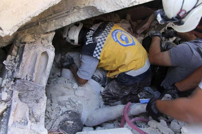 白盔隊隊員救出深埋瓦礫堆的死傷者。(AP)