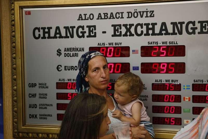 里拉危機是否擴散成市場焦點,圖為土耳其一處外匯兌換所,民眾持續關注里拉匯率。(AP)