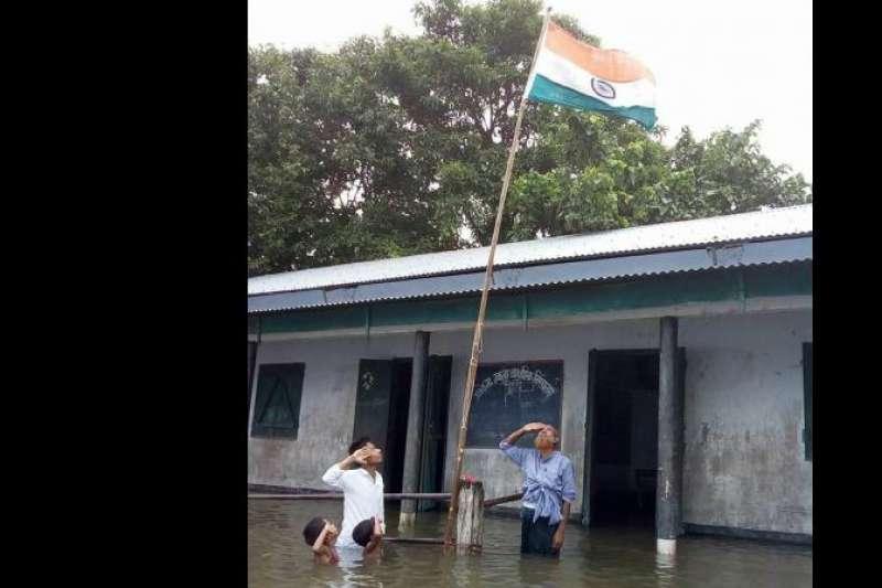 去年8月15日印度獨立70周年紀念日,可汗在小學參加升旗時,他、另外兩人、校長西克達站在水深及胸的操場向印度國旗敬禮,當時這張照片爆紅(Facebook/@Mizanur Rahman)