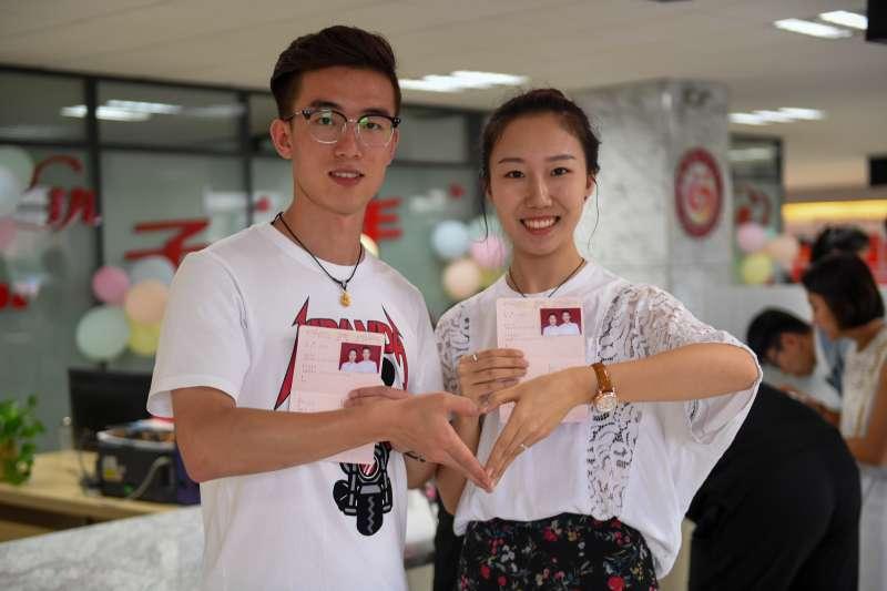 8月17日,在內蒙古呼和浩特市回民區市民服務中心內,一對新人領證後合影。當日是中國傳統節日七夕節,不少新人選擇在這一天登記結婚,讓這個浪漫的節日見證甜蜜的愛情。(新華社)