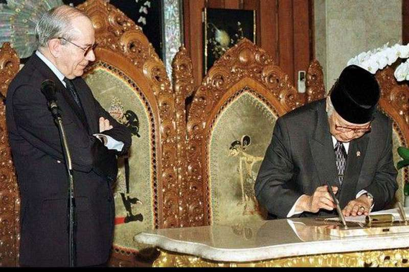 1998年任IMF總裁康德蘇(Michel Camdessus)雙手交叉於胸前,看著當時的印尼總統蘇哈托忍痛簽署紓困協議,要求大幅削減支出,進行改革。(美聯社)