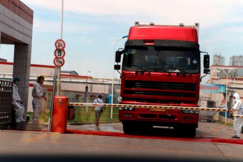 中國發現非洲豬瘟後,河南省鄭州肉類加工企業雙匯集團大門處可以看到身著防護服的工人。(美國之音)