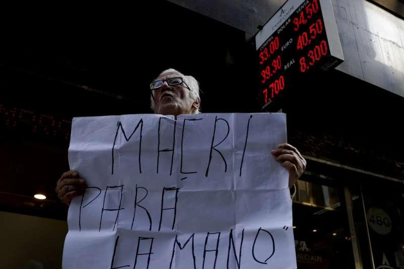 阿根廷披索狂貶,民眾手持標語抗議總統馬克里「停止吧,馬克里!」(AP)