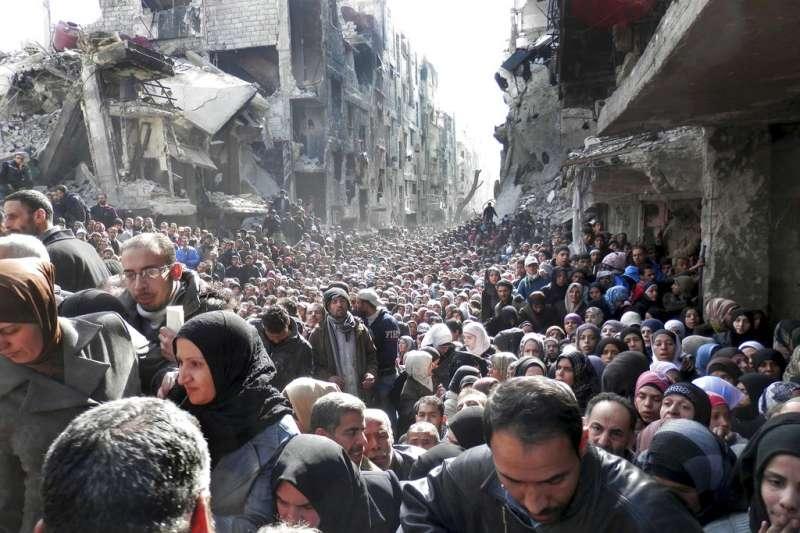 美國決定不再金援聯合國救濟工作處(UNRWA),中東情勢恐惡化。圖為2014年,敘利亞大馬士革的巴勒斯坦難民營,民眾排隊領取UNRWA發放的食物。(AP)