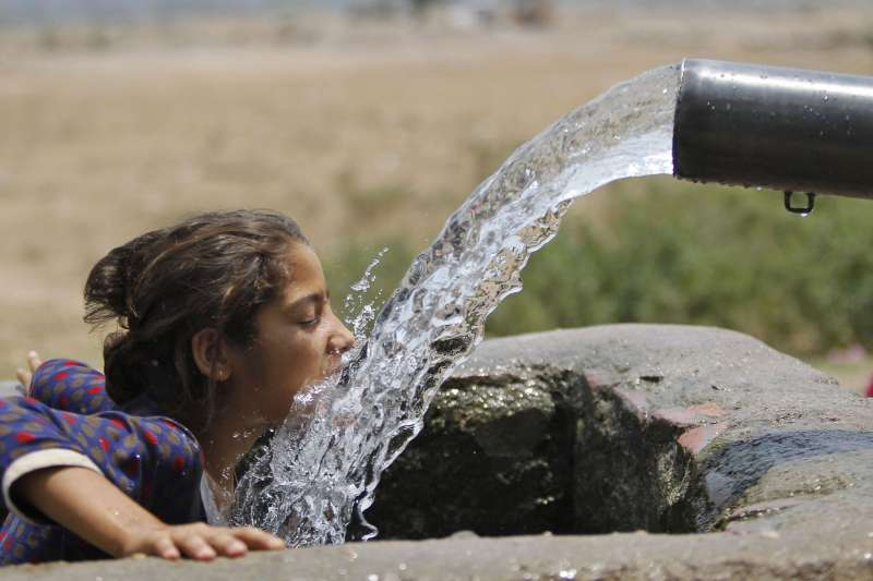 印度北部賈姆穆(Jammu)某個夏天的炎熱下午,一名女孩直接喝灌溉渠的水(美聯社)