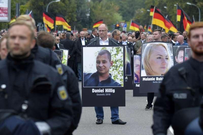 反對移民的右派支持者1日手持被害者照片,在肯尼茲遊行示威。據他們表示,這些人都是慘遭移民殺害的無辜民眾。(美聯社)
