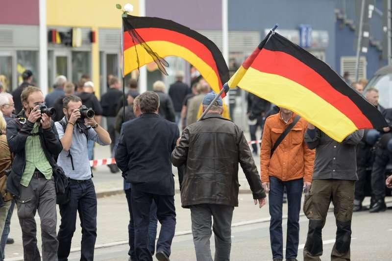 於德國肯尼茲9月1日爆發的示威中,左右派彼此對峙,右派民眾揮舞德國國旗,反對移民。(AP)