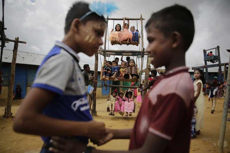 位於孟加拉難民營的羅興亞兒童在盪鞦韆前玩樂。(美聯社)