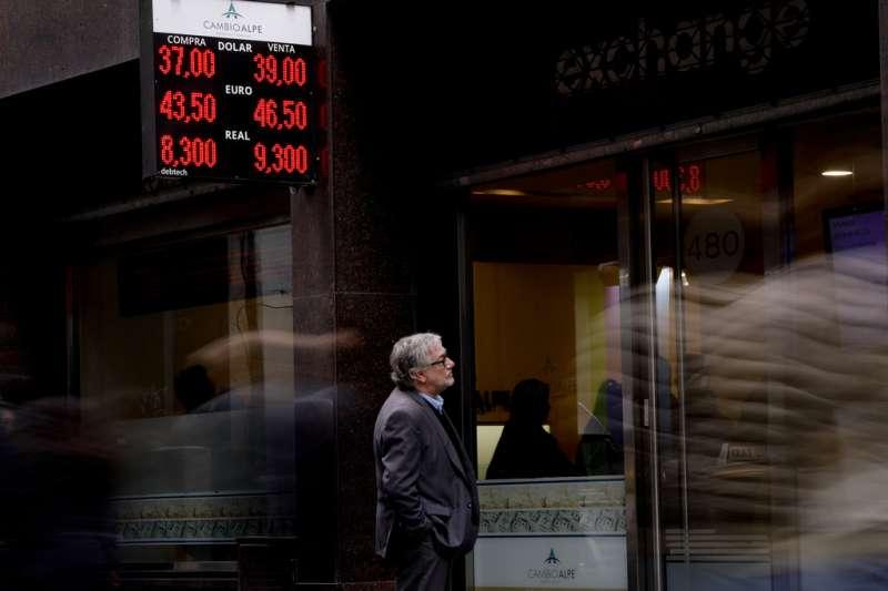 一位民眾在布宜諾艾利斯街頭駐足,仔細端詳阿根廷披索的匯率走勢。(美聯社)