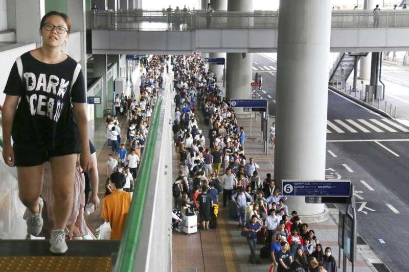 颱風燕子4日侵襲日本,關西國際機場淹水癱瘓。圖為等待搭乘接駁巴士、等待離開關西機場的旅客。(美聯社)