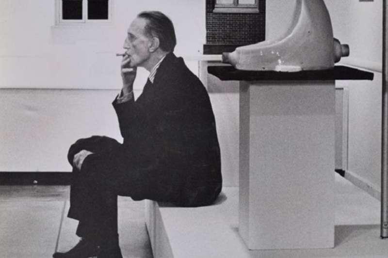 杜象老年時,與自己的作品《噴泉》合照。由Julian Wasser所攝。 (來源:Robert Berman Gallery)