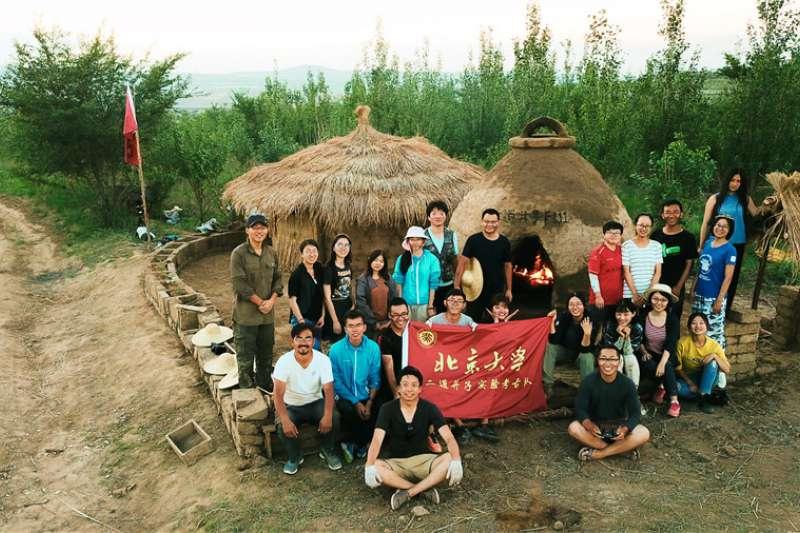 「東方龐貝城」二道井子實驗考古隊員們在完工的史前房子前合影。(新華社)
