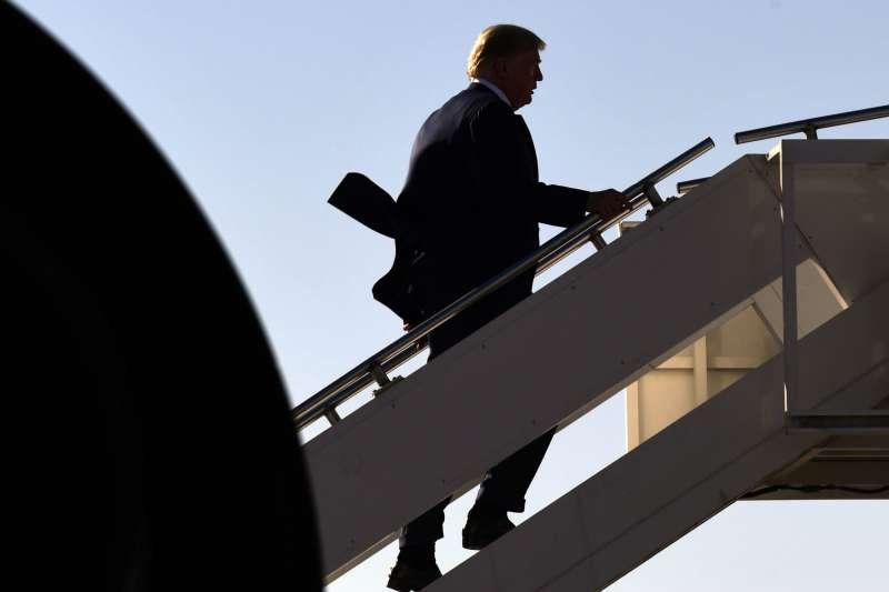 美國總統川普登上空軍一號,衣襬側影讓他看似拿著一把步槍登機(AP)